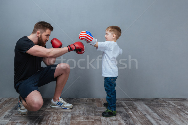 Father and little son working out in boxing gloves together Stock photo © deandrobot