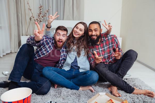Tres sonriendo amigos sesión habitación Foto stock © deandrobot