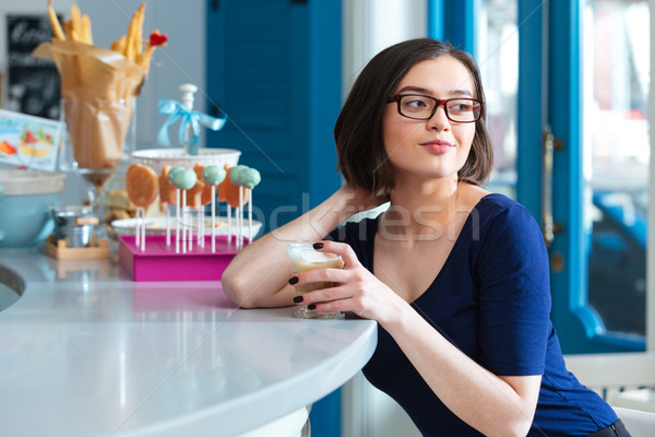 Happy woman drinking latte at bar counter in cafe Stock photo © deandrobot
