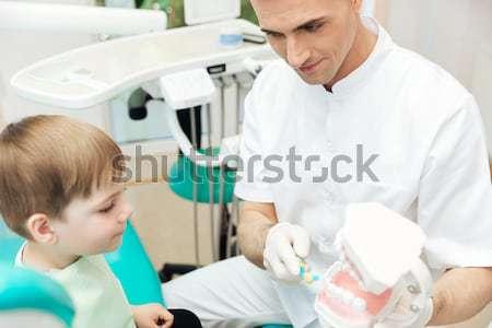 Stock photo: Smiling dentist doing dental treatment to little boy