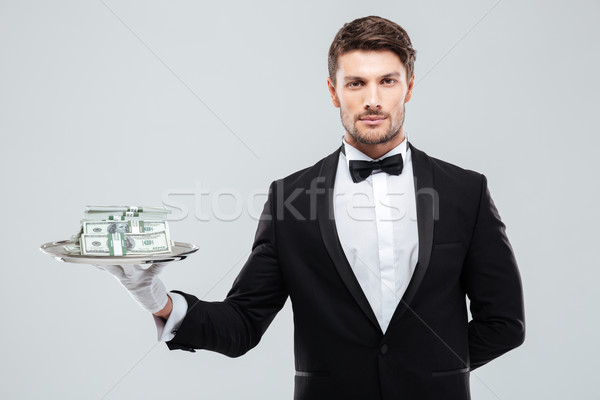 Handsome waiter in tuxedo standing and holding money on tray Stock photo © deandrobot