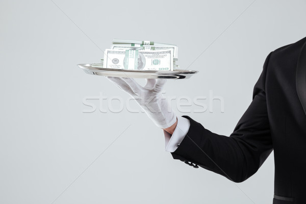 Tray with money holded by waiter hand in glove Stock photo © deandrobot