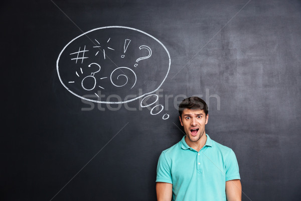 Confused man thinking about problem with blackboard behind him Stock photo © deandrobot