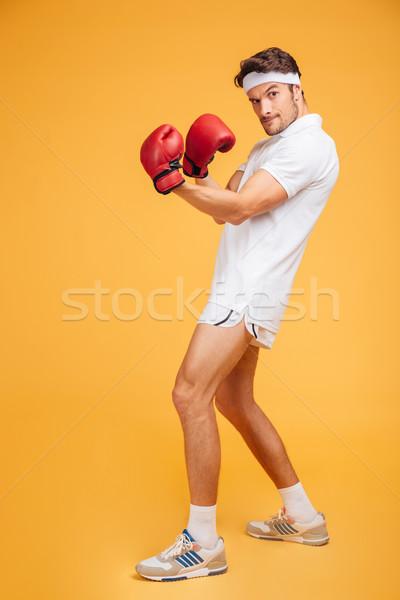 Erős fiatalember boxoló piros kesztyű áll Stock fotó © deandrobot