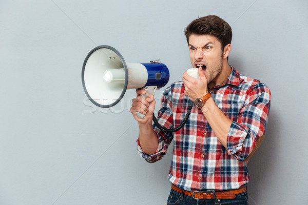 Irritated angry young man in plaid shirt shouting with loudspeaker Stock photo © deandrobot