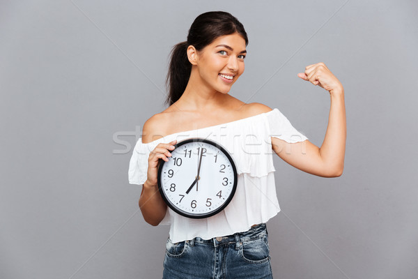 Smiling businesswoman holding clock and showing biceps Stock photo © deandrobot