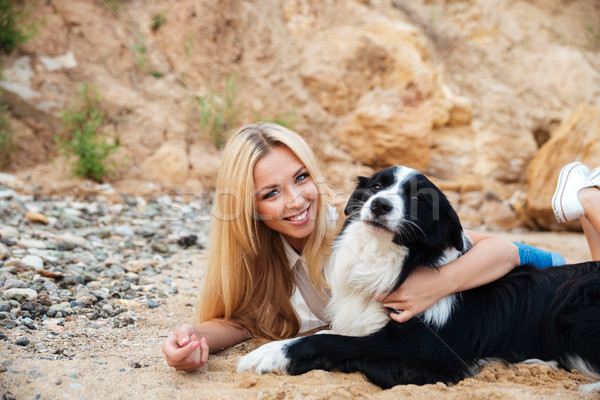 Cheerful woman resting and hugging her dog on the beach Stock photo © deandrobot