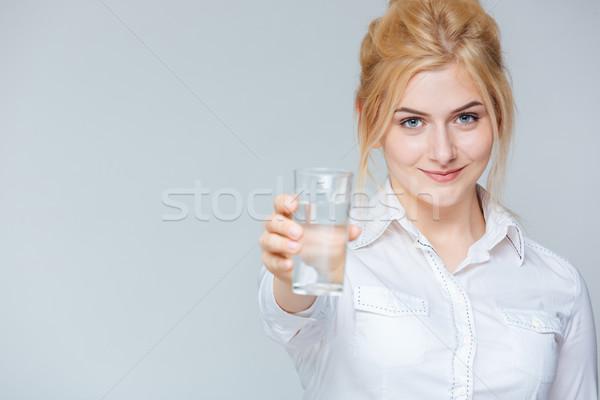 Mosolyog aranyos fiatal üzletasszony üveg víz Stock fotó © deandrobot