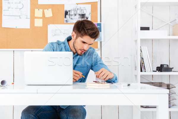 Handsome young businessman sitting and signing documents Stock photo © deandrobot