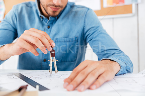 Architect working on construction blueprint in office with divider Stock photo © deandrobot