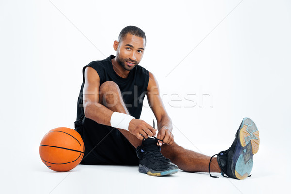 Handsome young man basketball player sitting and tying laces Stock photo © deandrobot