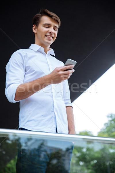 Stockfoto: Glimlachend · aantrekkelijk · jonge · zakenman · permanente · smartphone