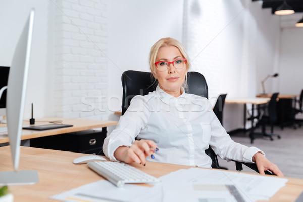 портрет улыбаясь зрелый деловая женщина используя ноутбук служба Сток-фото © deandrobot