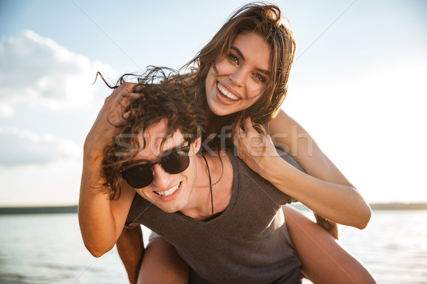 Young happy couple piggyback at the beach Stock photo © deandrobot