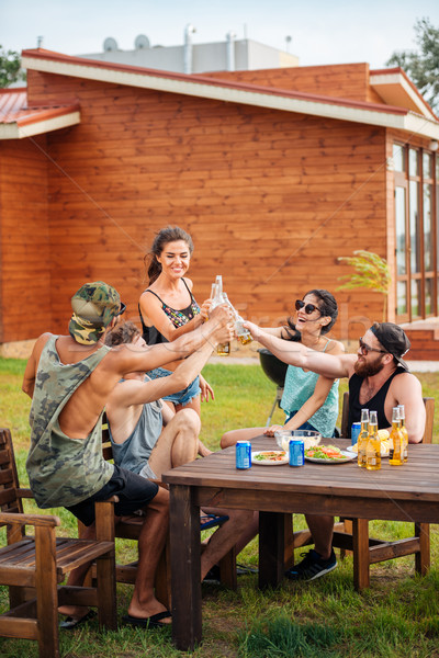Cheerful friends sitting at table drinking beer and having fun Stock photo © deandrobot