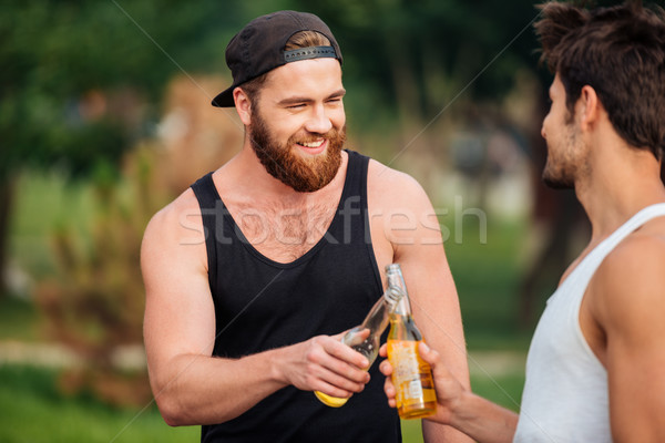 Two men holding a beer bottles outdoors Stock photo © deandrobot