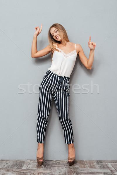 Sorridente mulher bonita em pé indicação para cima tanto Foto stock © deandrobot