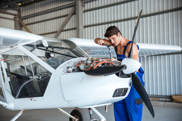 Aircraftsman repairing small aircraft Stock photo © deandrobot