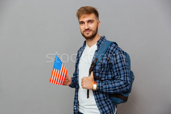 Bearded man standing with backpack and holding USA flag Stock photo © deandrobot