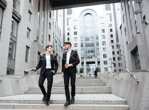 Two businessmen walking and talking near business center Stock photo © deandrobot
