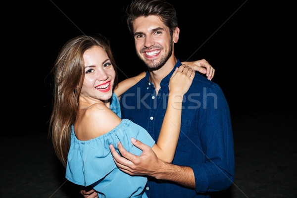 Cheerful beautiful young couple standing on the beach at night Stock photo © deandrobot
