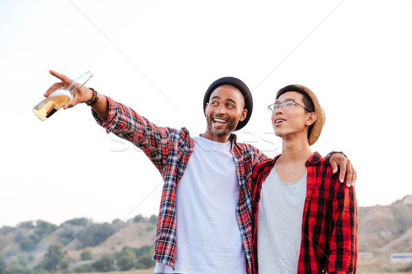 Two happy men looking and pointing away outdoors Stock photo © deandrobot