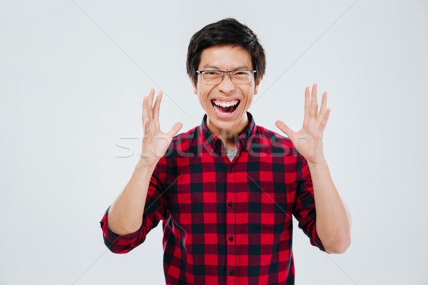 Screaming young asian man gesturing with hands Stock photo © deandrobot