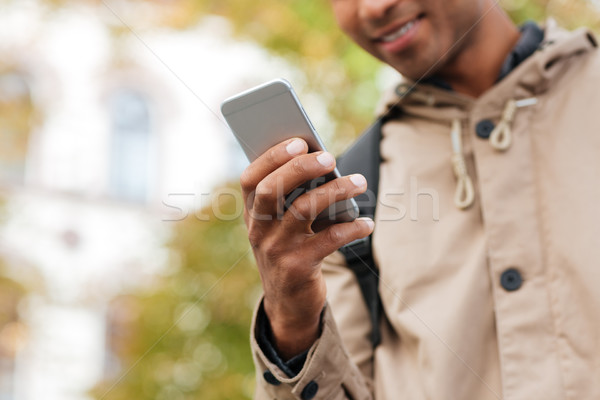 Young dark skinned man using his cellphone on the street Stock photo © deandrobot