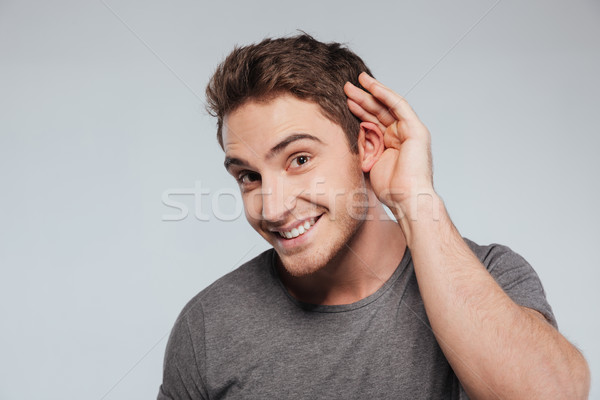Portrait of young casual man which overhears conversation Stock photo © deandrobot