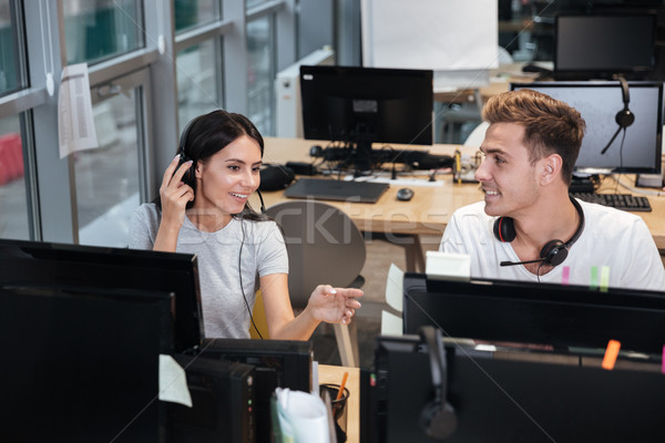 Young Coworkers sit by the table in headphones Stock photo © deandrobot