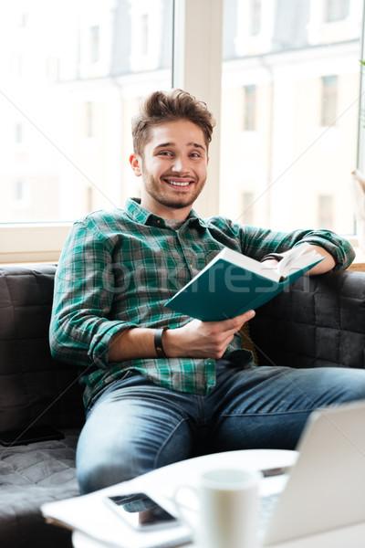 Man reading book near the table Stock photo © deandrobot