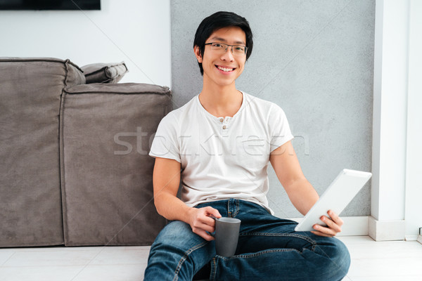 Asian man sitting with coffee and tablet Stock photo © deandrobot