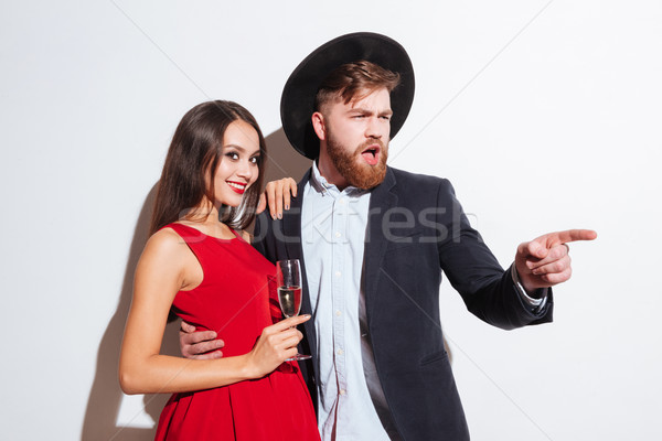 Happy beautiful young couple drinking champagne and pointing away Stock photo © deandrobot