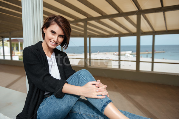 Smiling beautiful young woman sitting in arbour on the seaside Stock photo © deandrobot