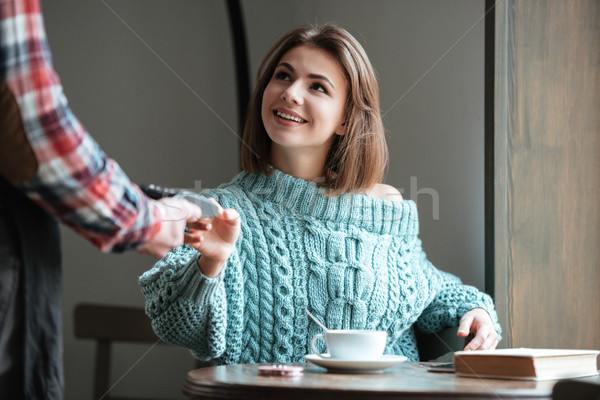 Happy young woman pays for her order with debit card. Stock photo © deandrobot