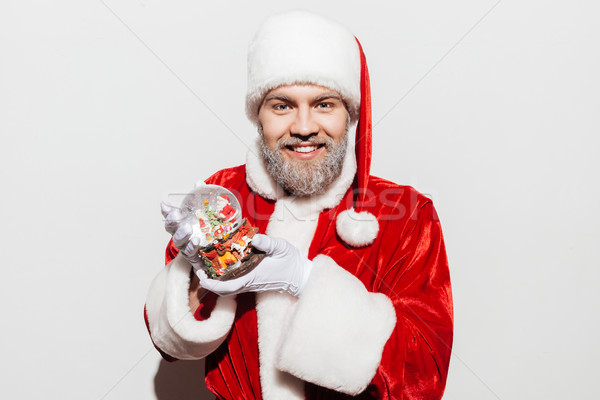 Happy man santa claus smiling and holding snow ball Stock photo © deandrobot