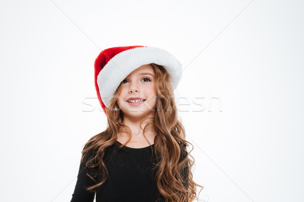 Cheerful little girl with curly hair in santa claus hat Stock photo © deandrobot