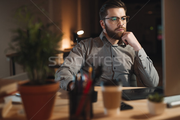 Handsome bearded web designer working late at night Stock photo © deandrobot