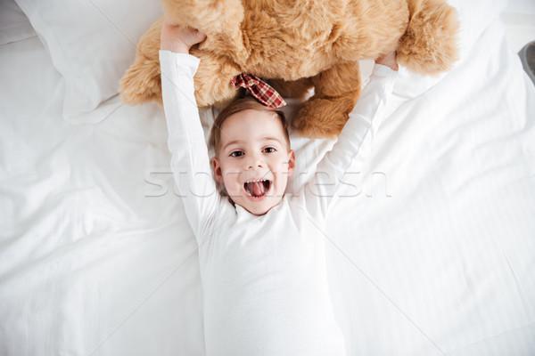 Radosny mały chłopca leży bed Zdjęcia stock © deandrobot