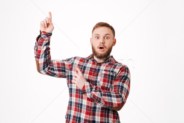 Man in shirt pointing up Stock photo © deandrobot