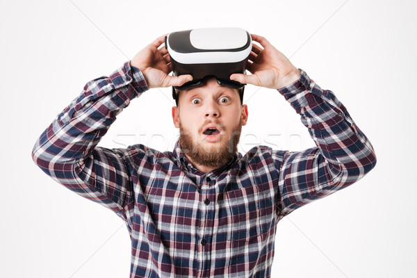 Surprised Bearded man in shirt takes off virtual reality device Stock photo © deandrobot