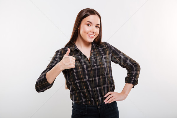 Smiling Woman showing thumb up with arm at hip Stock photo © deandrobot