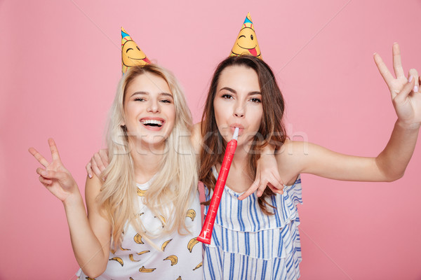 Two smiling pretty young women celebrating birthday and having fun Stock photo © deandrobot