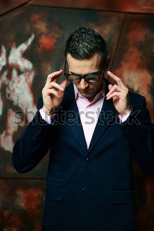 Man sitting on bench and talking on mobile phone outdoors Stock photo © deandrobot