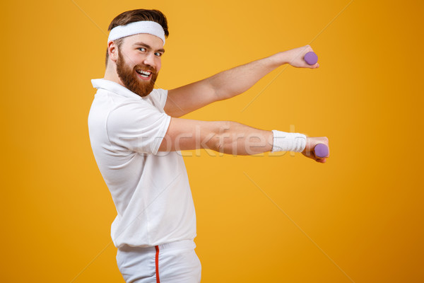 Side view of smiling sportsman with lightweight dumbbells Stock photo © deandrobot