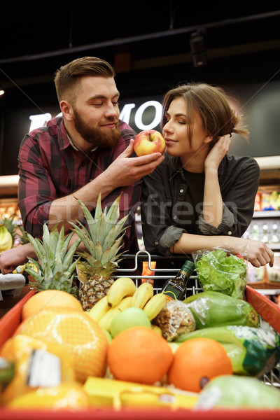 Cheerful young loving couple in supermarket smelling fruits Stock photo © deandrobot