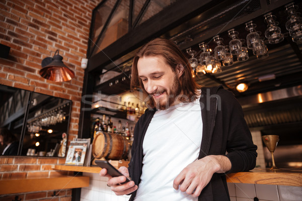 View from below of man on bar with phone Stock photo © deandrobot