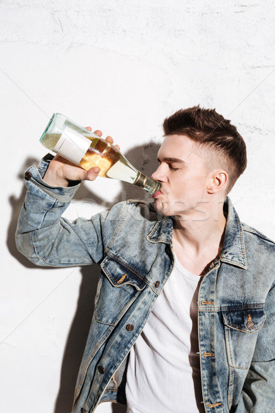 Handsome man standing on floor drinking alcohol Stock photo © deandrobot