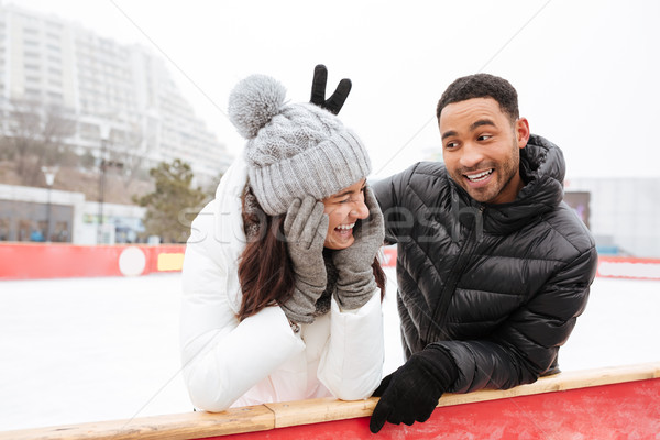 Happy funny loving couple skating at ice rink outdoors. Stock photo © deandrobot