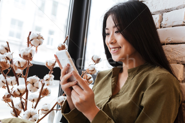 Stock photo: Cheerful asian young lady chatting by her mobile phone
